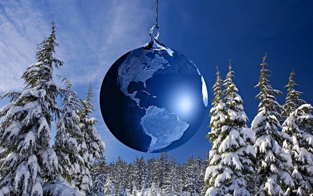 Earth as blue Christmas ornament hanging in winter scene