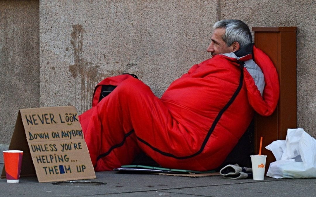 Homeless man in orange sleeping bag on street