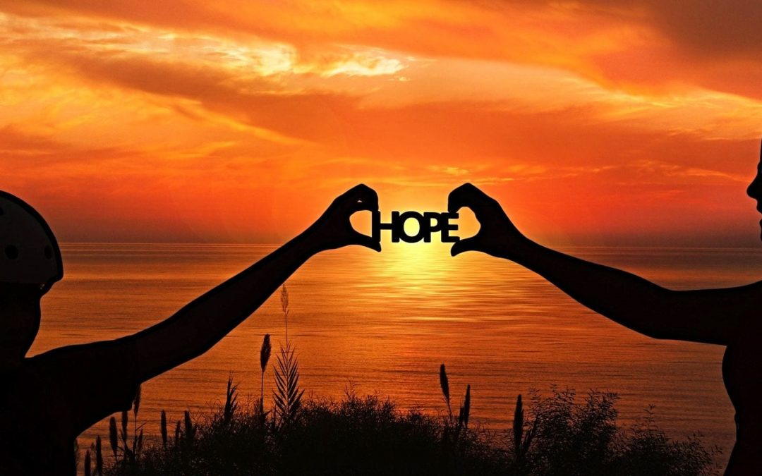 Two people holding up the word 'hope' at sunrise