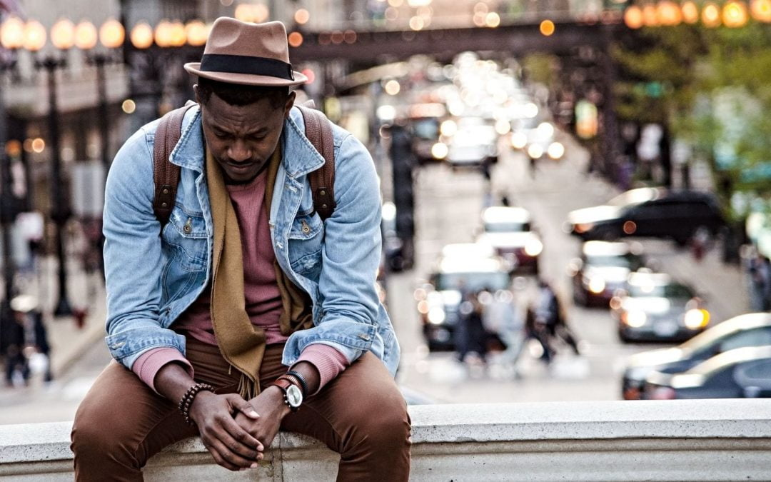 Dejected man sitting on bench in the city