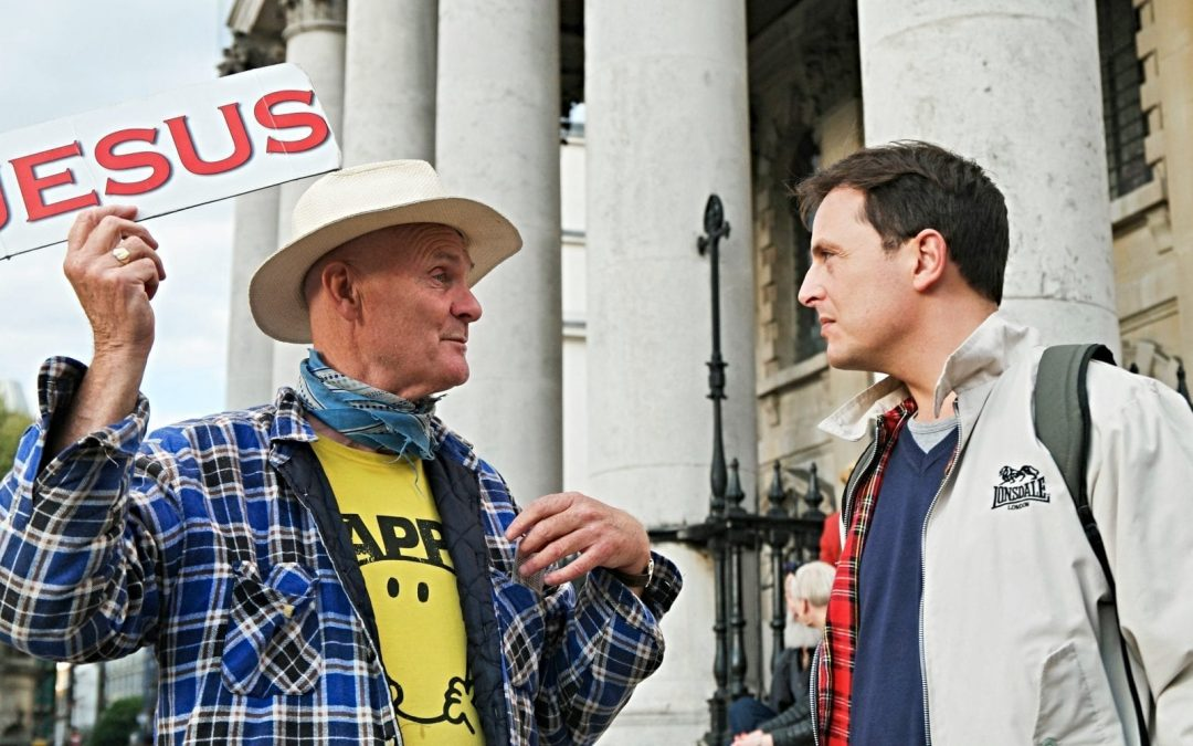 Street evangelist holding 'Jesus' signing and talking to passer-by