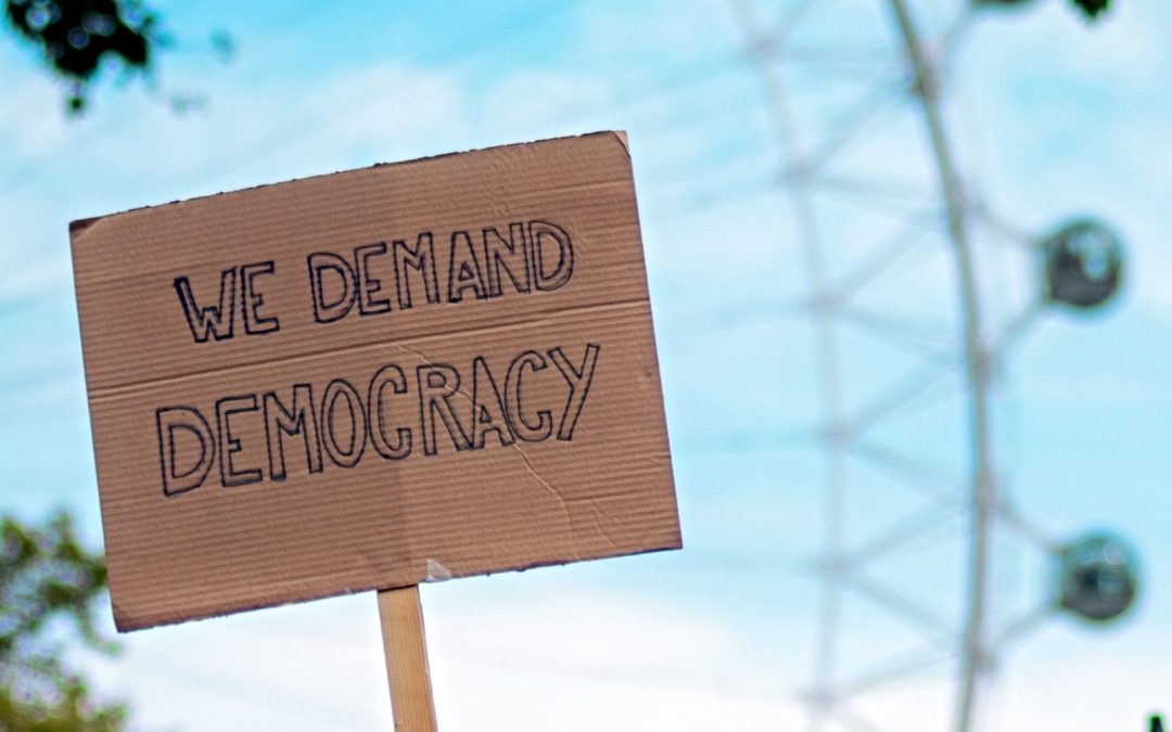 Cardboard protest sign reading 'We demand democracy'