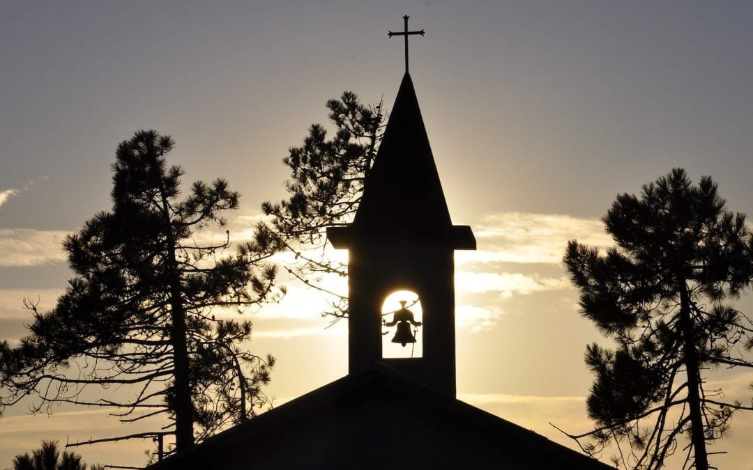 Church steeple with sun in the background