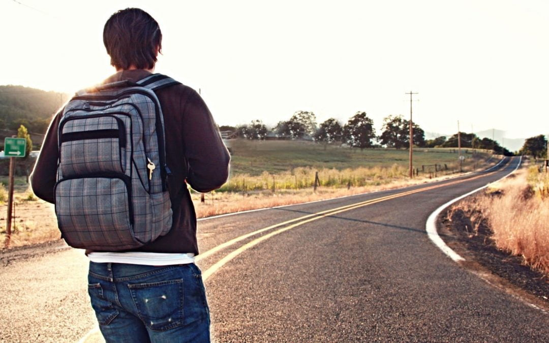 Young man with backpack hiking along a roadway