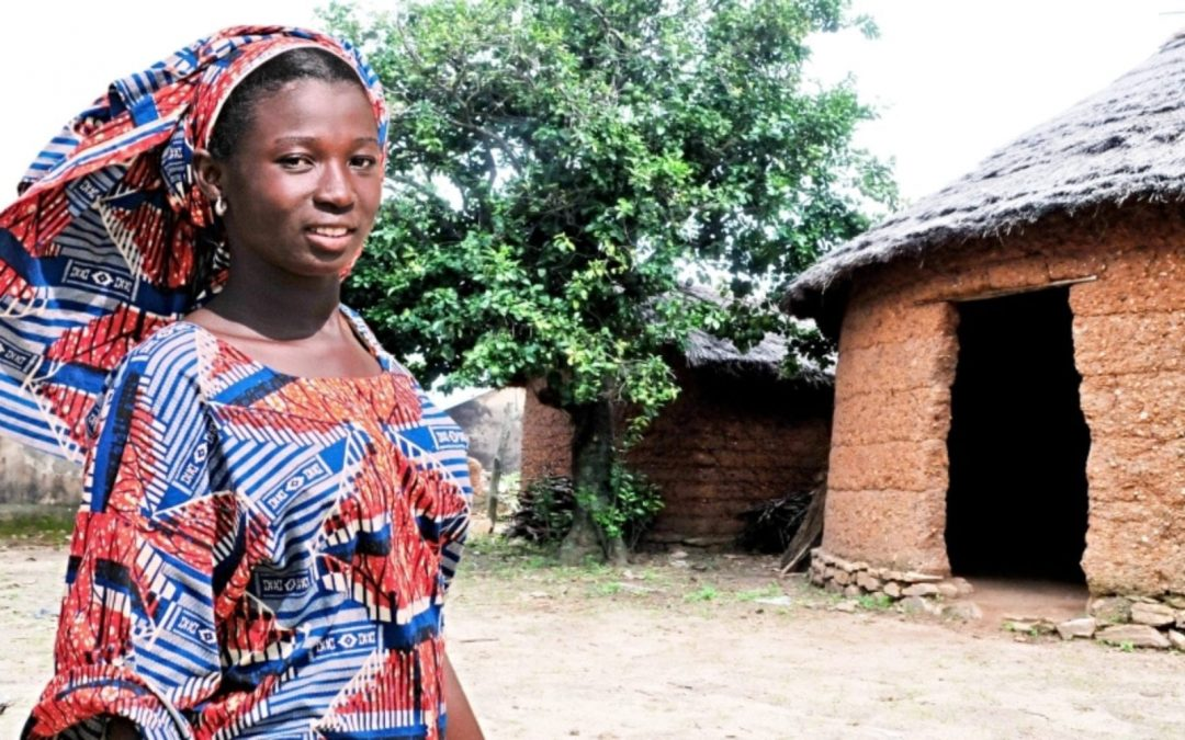 African woman standing outside village structure