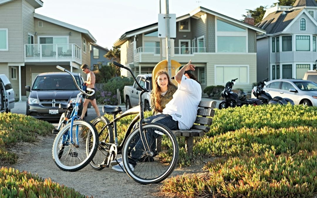Bicyclists sitting on bench in neighborhood