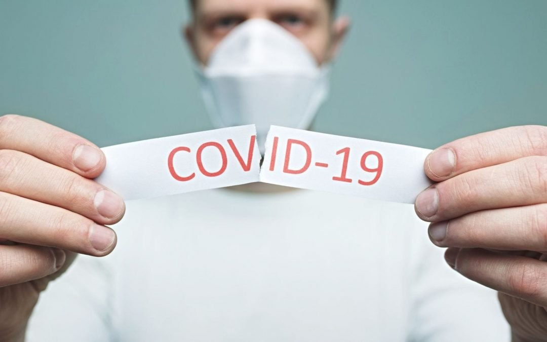 Masked medical worker ripping COVID-19 paper