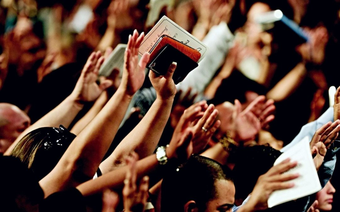 People raising hands in church and holding Bibles