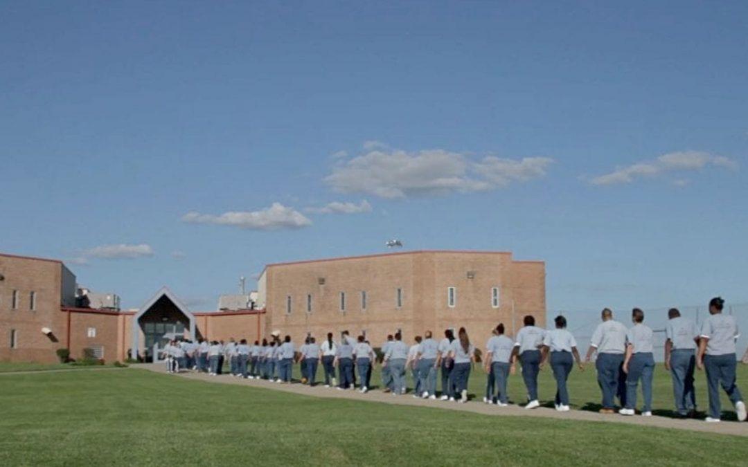 Prisoners outdoors walking in single file