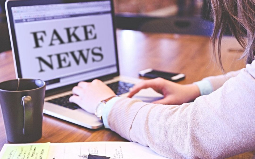 Woman working at desk with laptop displaying words 'fake news'