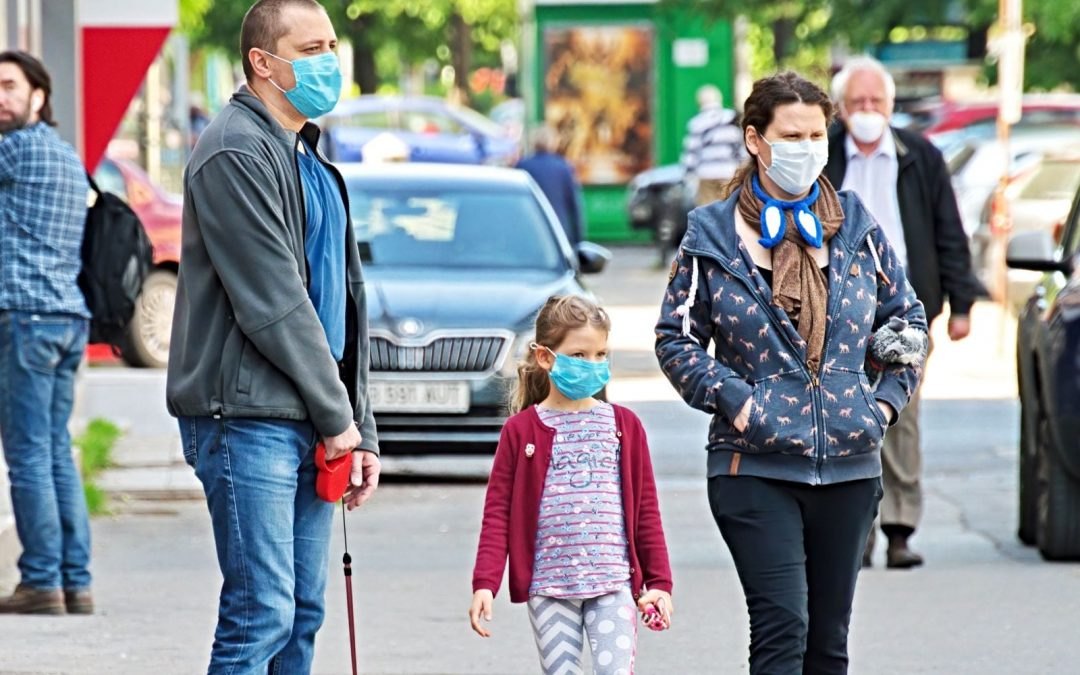 Parents and daughter outside wearing masks