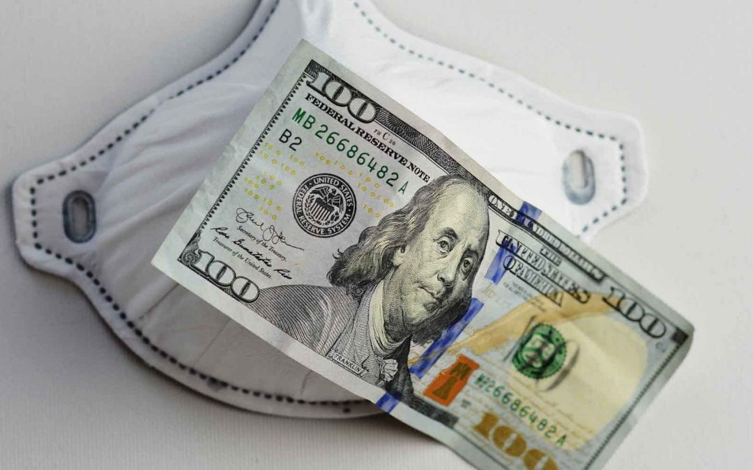 A $100 bill sitting on top of a medical mask.