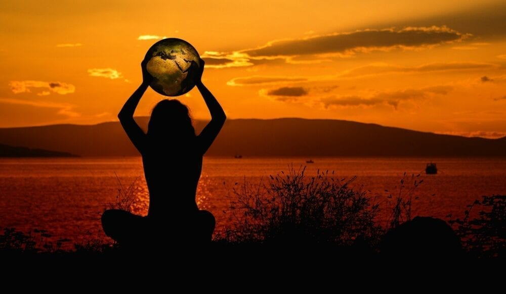 A woman holding a globe watching the sunset