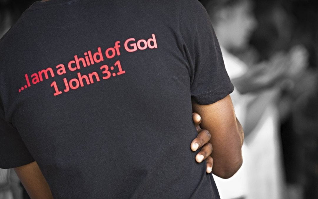 Black person wearing T-shirt with 1 John 3:1