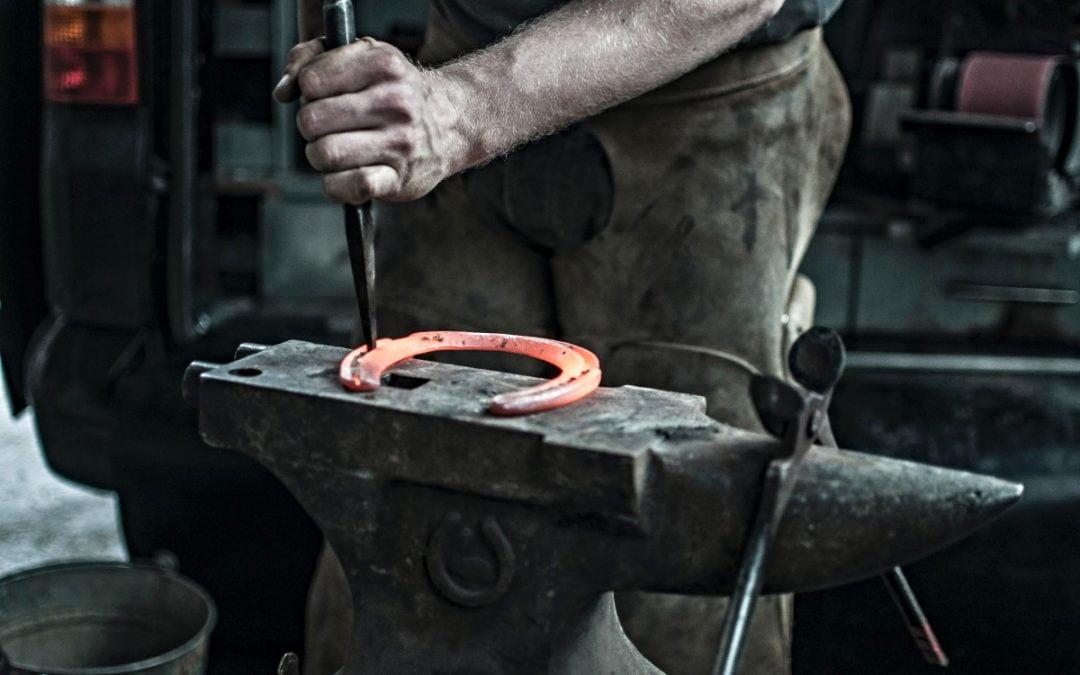 Man fashioning horseshoe on anvil