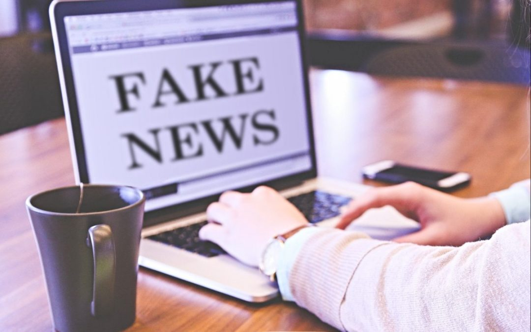 Man typing on laptop with words 'fake news'