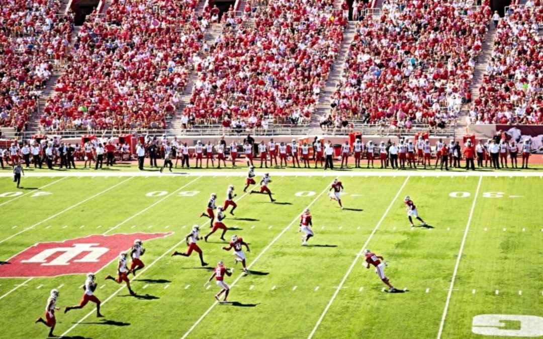 Football players playing in a packed stadium