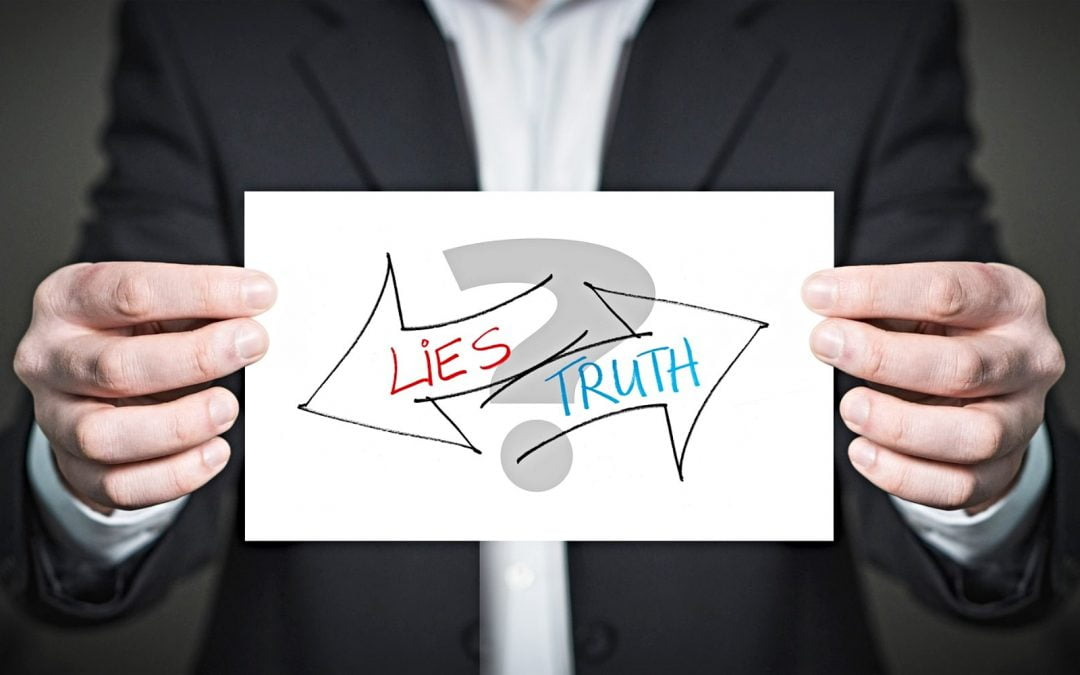 Man holding sign with two arrows labeled 'lies' and 'truth' over question mark