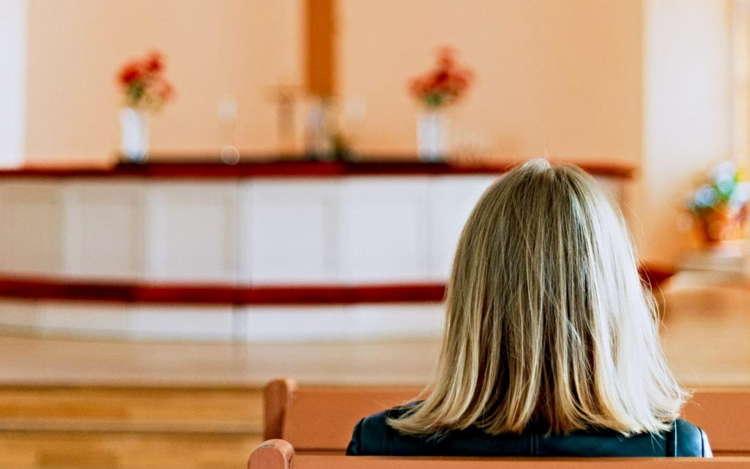 View from back of woman's head seated in pew