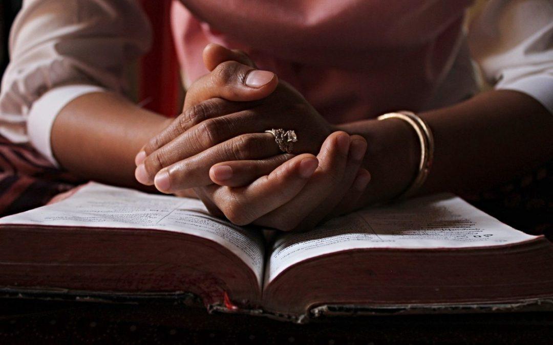 Crossed hands on open Bible