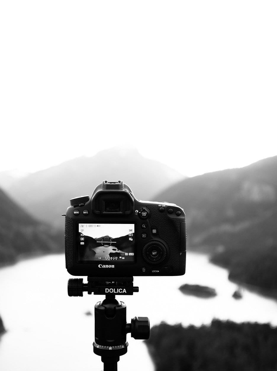 A camera taking a photo of a lake with mountains in the background