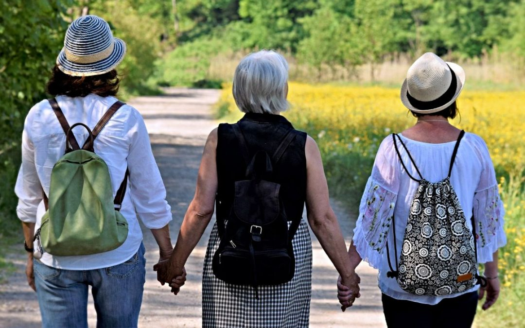 Three women friends holding hands as they walk down a road