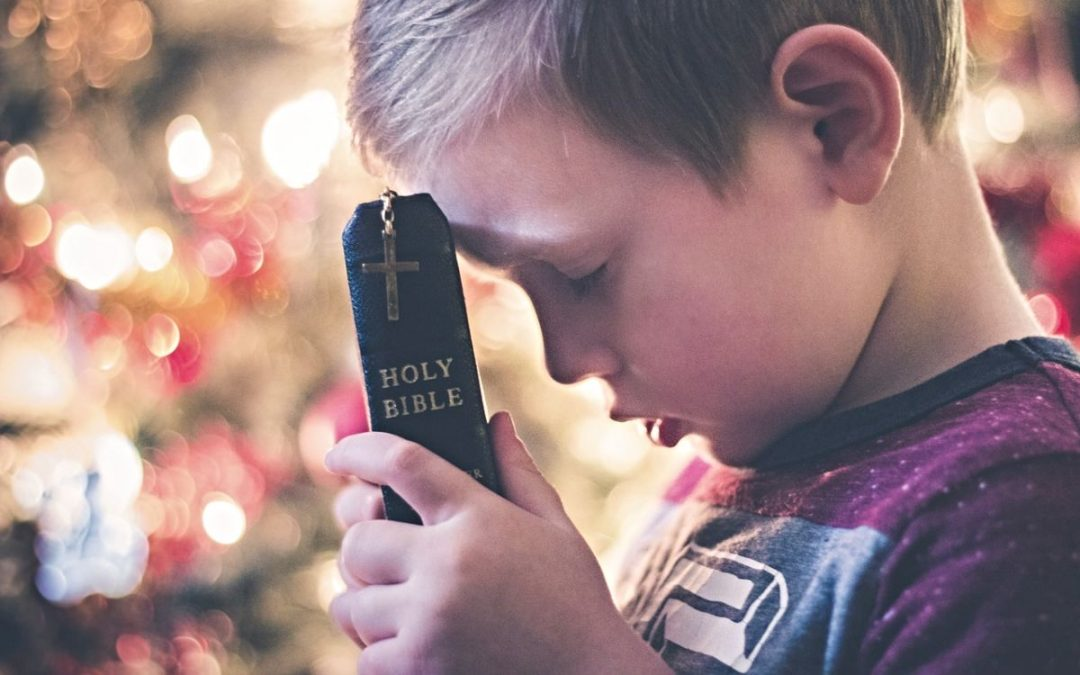 Boy praying with bible against forehead