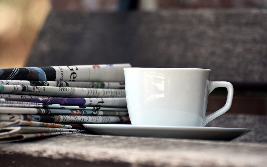 White coffee cup on a table next to a stack of newspapers