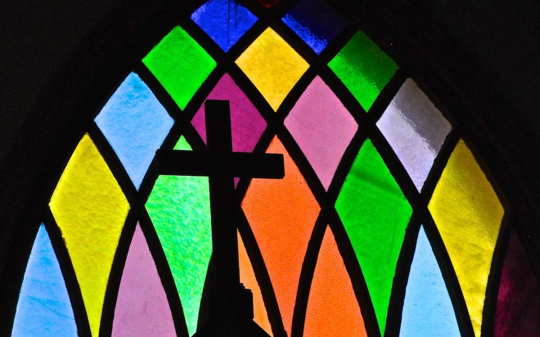 Silhouette of cross in front of stained-glass window