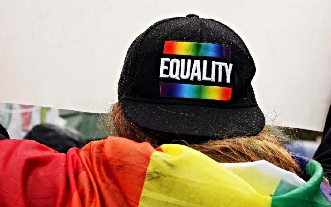 Person wearing cap with word Equality and rainbow bars