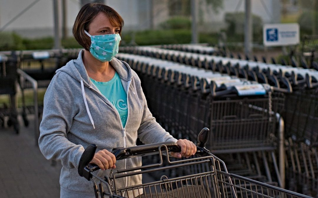 Woman wearing mask pushing grocery cart