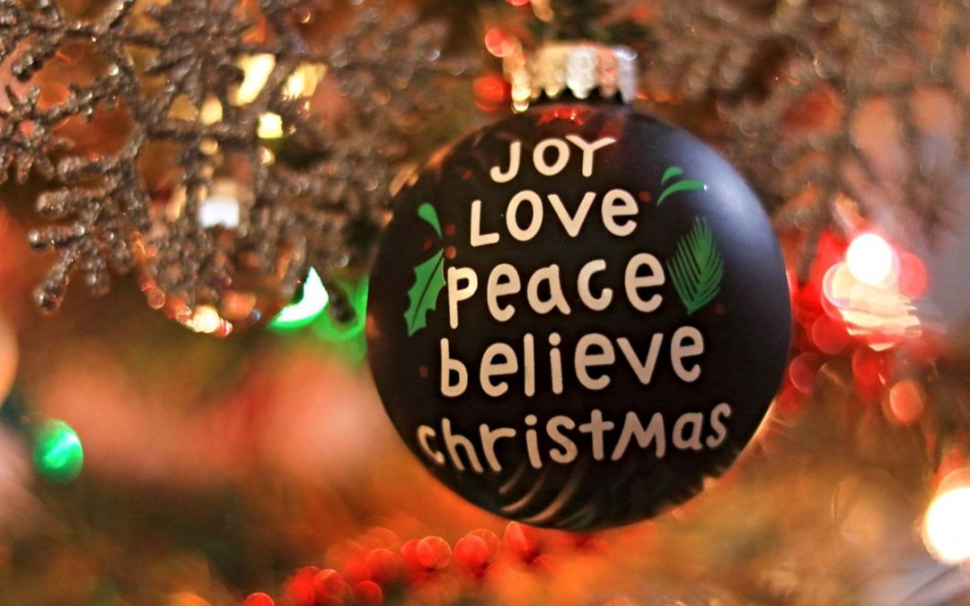Ornament on Christmas tree with words 'joy, love, peace, Christmas, believe'