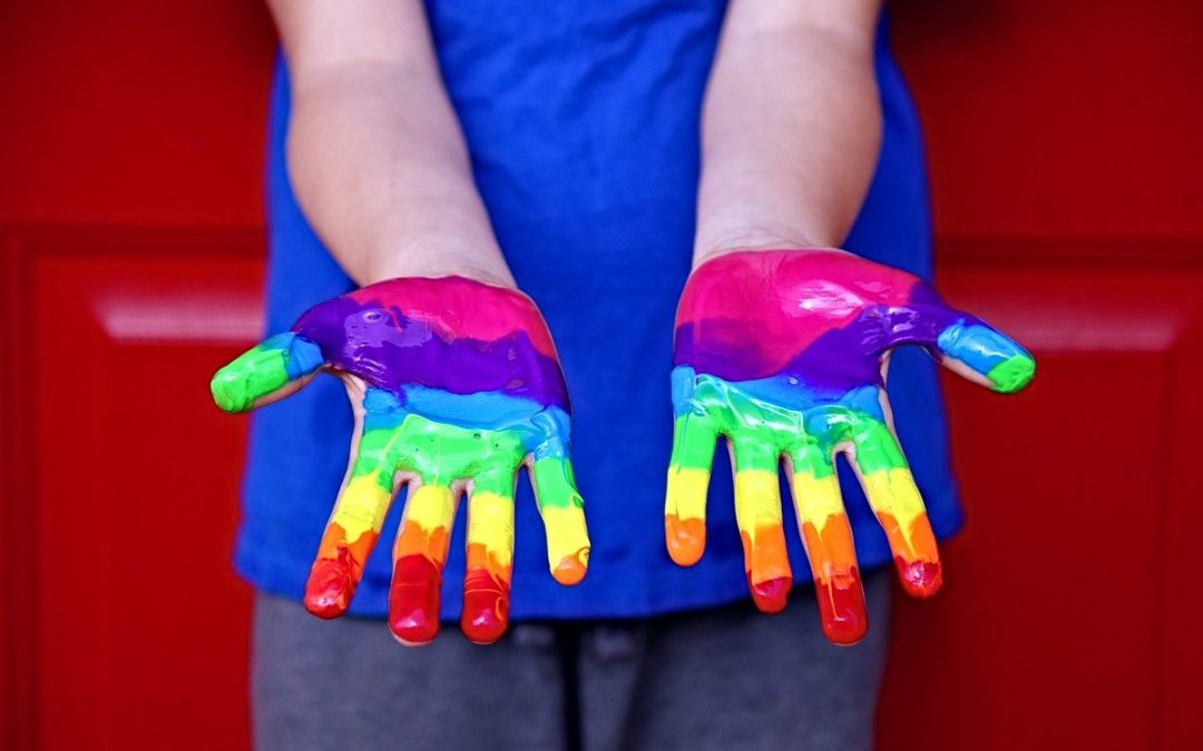 Pair of hands with LGBTQ rainbow painted on them