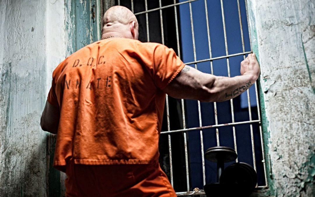 Prisoner in orange jumpsuit at barred windows
