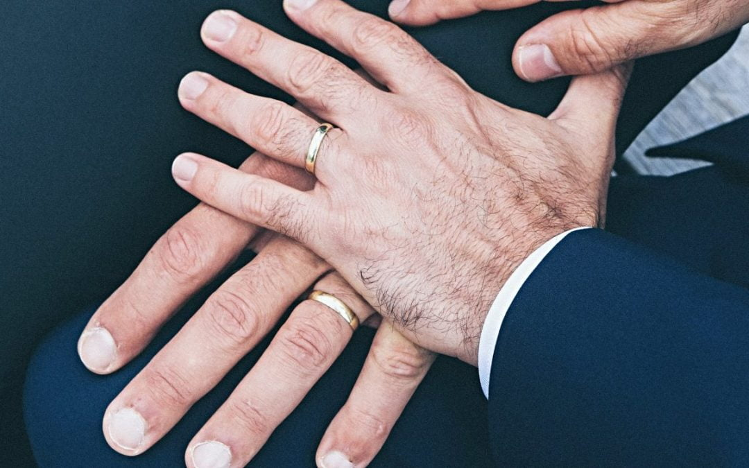 Two male hands with wedding bands