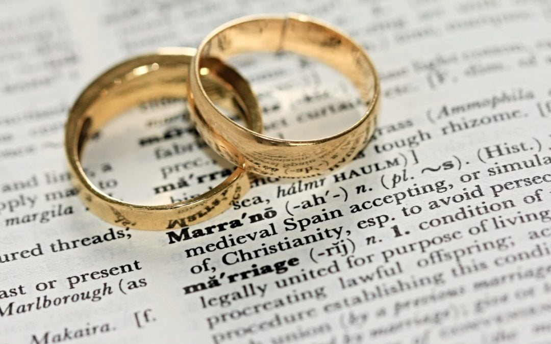 Two wedding rings on dictionary definition of marriage