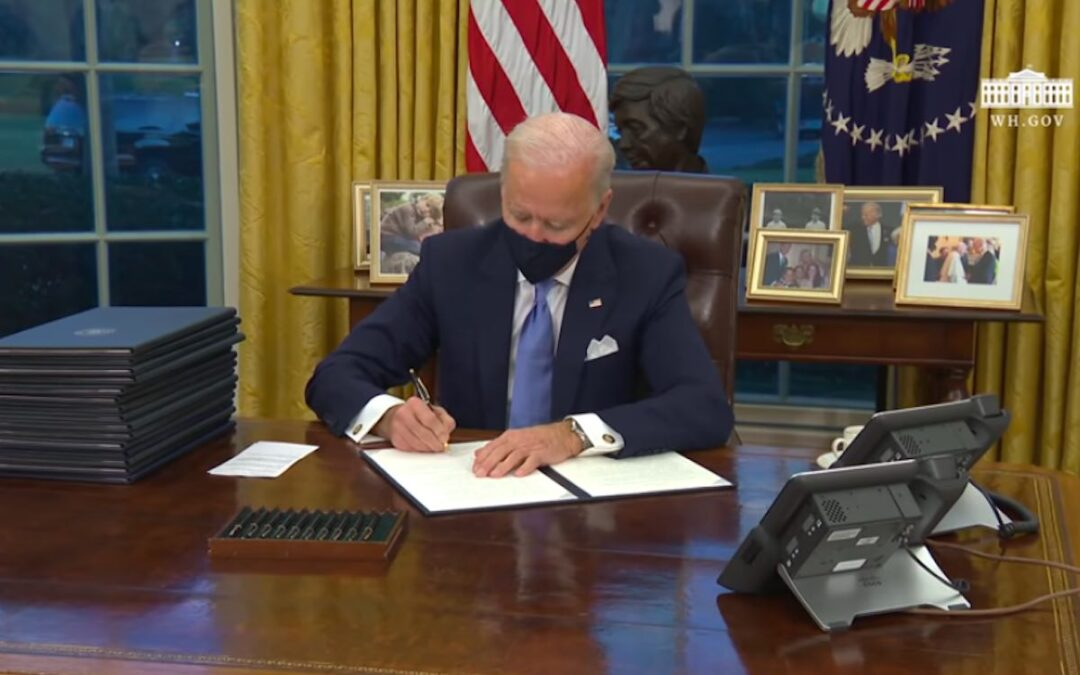 President Biden signing executive orders.