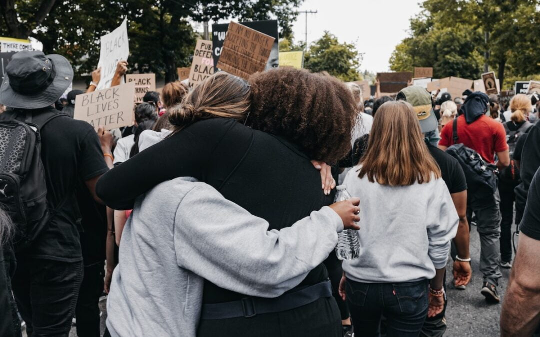 Two women hugging at a Black Lives Matter protest.
