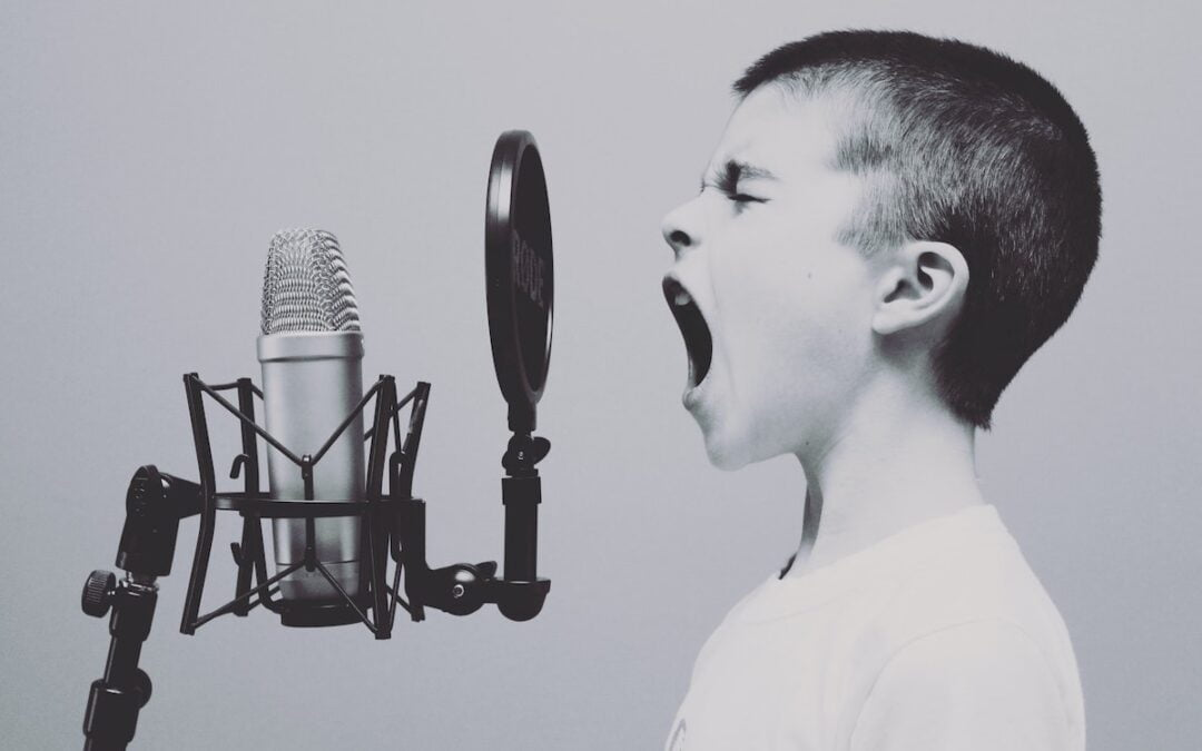 A young boy yelling into a microphone.