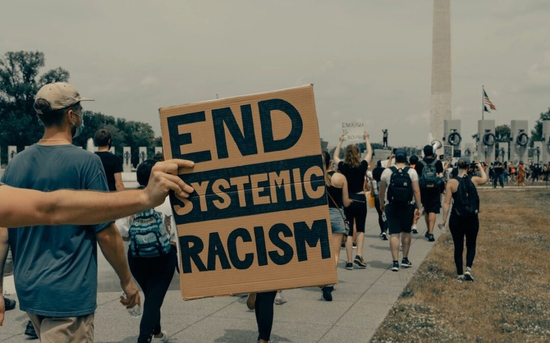 "A line of people walking down a sidewalk with someone holding a sign that says, ""End Systemic Racism."""
