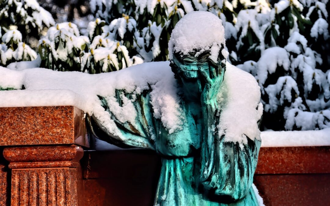 A statue with bowed head covered in snow.