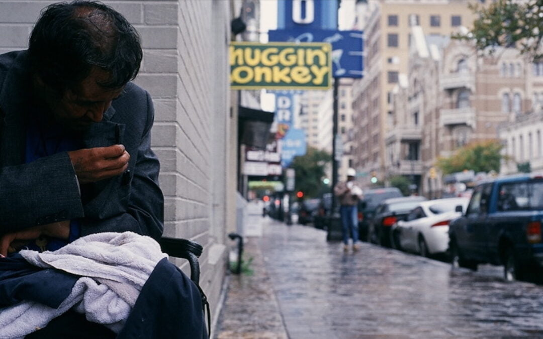 A homeless man sitting on a sidewalk in downtown Austin, Texas.