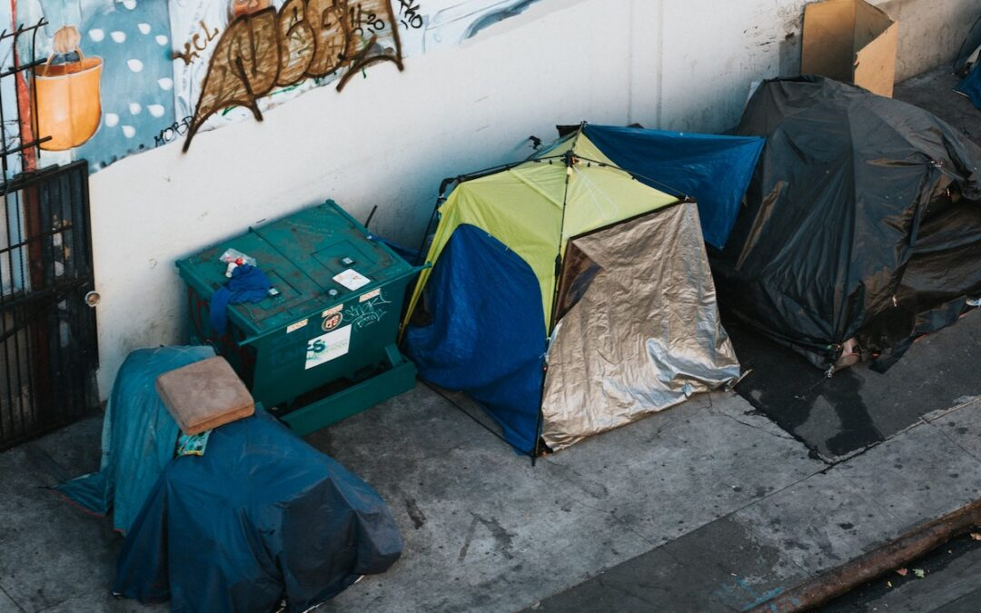 A row of tents on a sidewalk in a city.