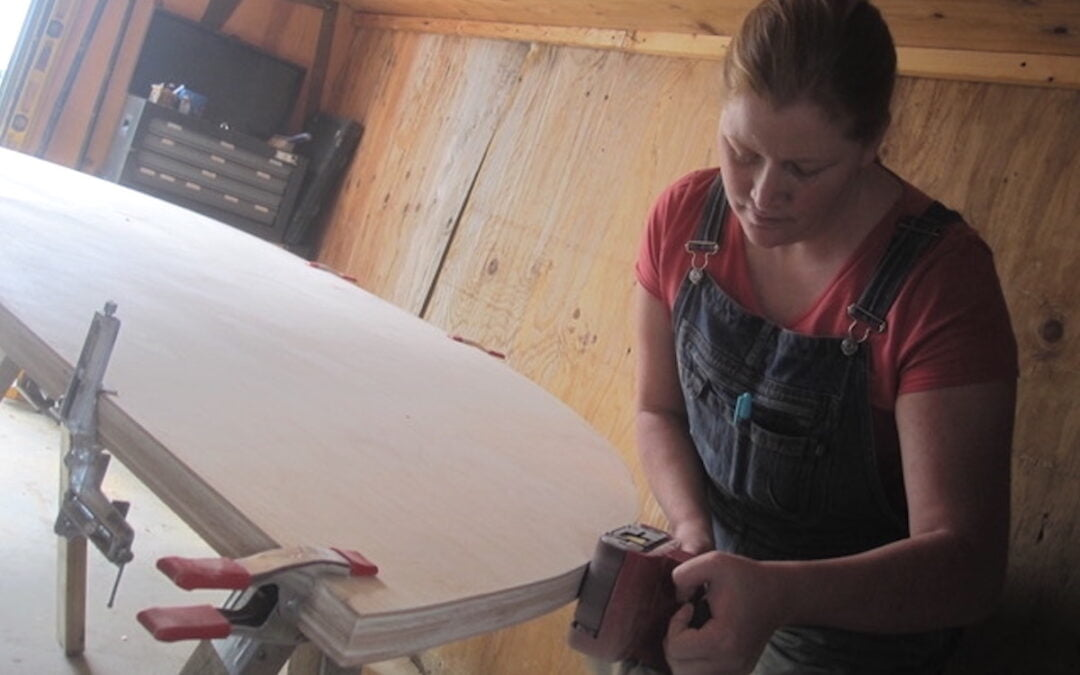 A woman sanding down a table.