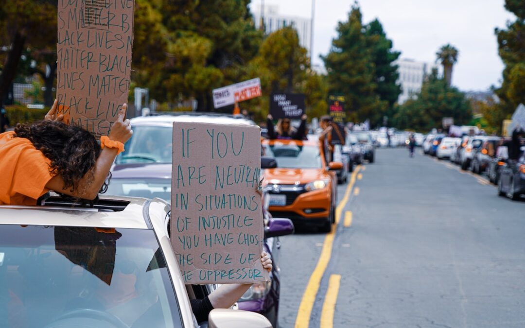 Two people in a car holding cardboard signs out the window during a demonstration for racial justice.