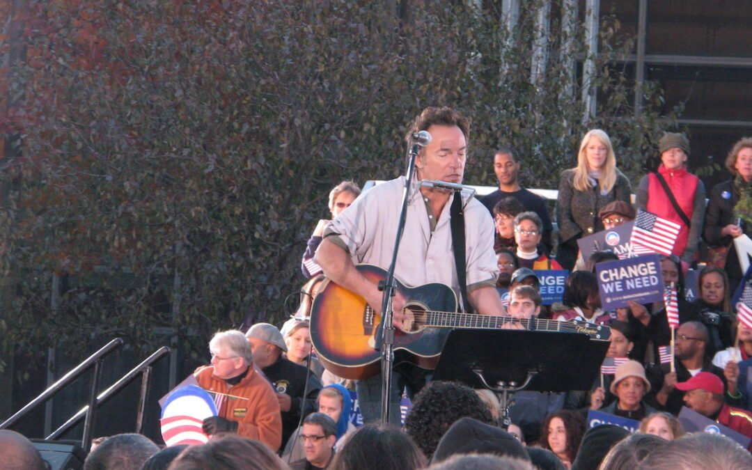 Bruce Springsteen performing on stage with an acoustic guitar.