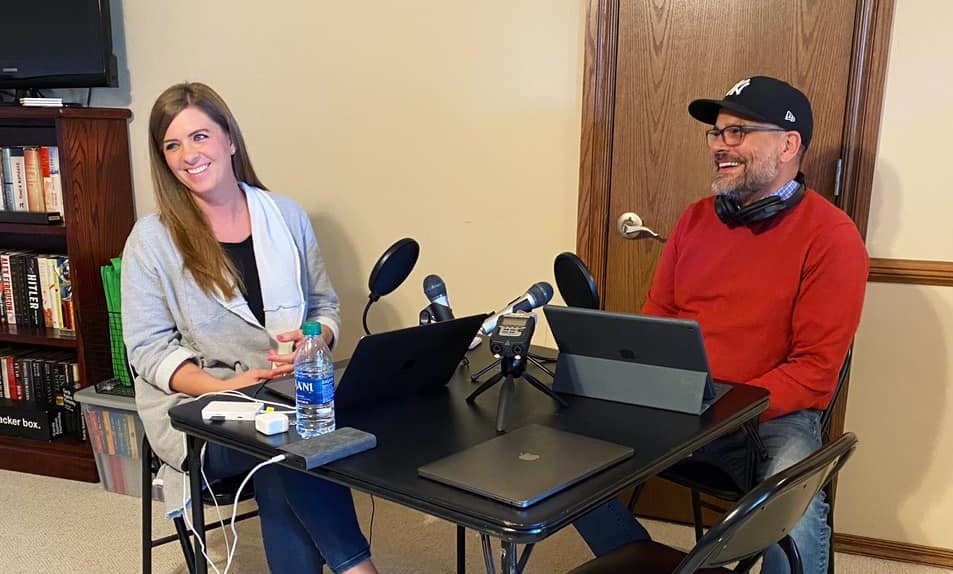 Two people sitting at a table recording a podcast.