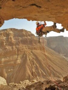 A man repelling down into a cave.