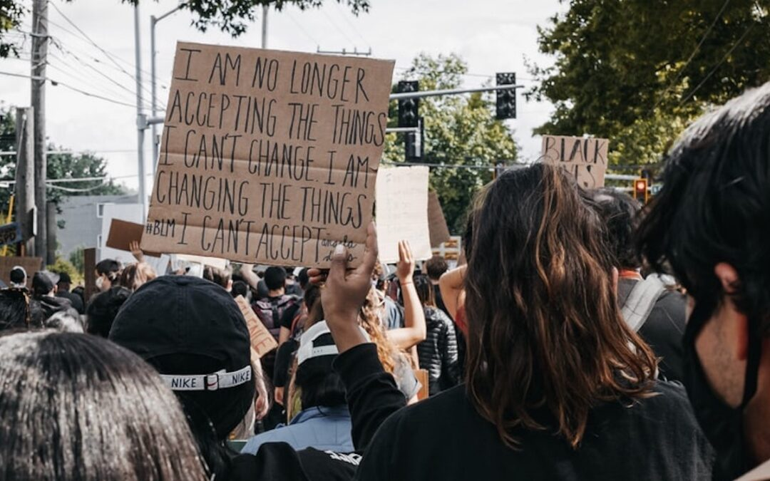 """A person in a crowd of people holding a sign that says, """"I'm no longer accepting the things I can't change. I'm changing the things I can't accept."""""""