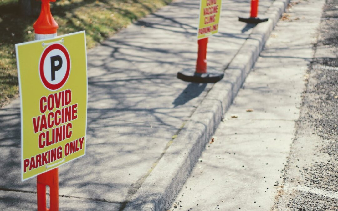 A row of signs designation parking space for COVID-19 vaccine patients.